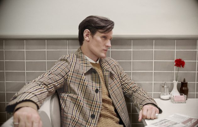 Matt Smith wears a check car coat with a cashmere cable-knit sweater c Courtesy of Burberry